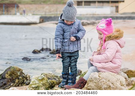 two small kids playing together outdoors. siblings exploring seaside. two preschoolers actively playing on stony beach countryside life with children.