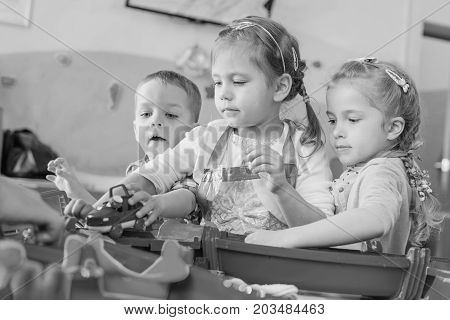Three little kids play with water and toys ( black and white )