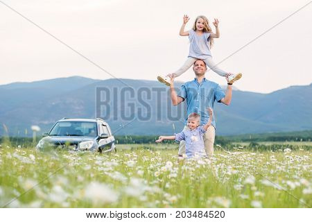 Father and children on offroad car playing in the field after sunset. People having fun on the field. Concept of friendly family and of summer vacation.