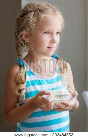 cute little girl eats cottage cheese for breakfast