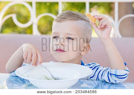 happy little boy eating soup in the cafe. outdoor