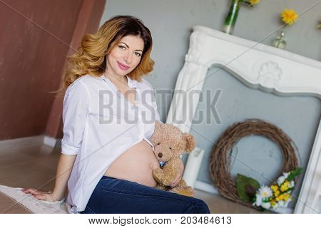 Pregnant woman with a bear sitting on a knitted plaid