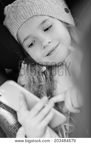 toddler girl is playing smartphone in the car (black and white)