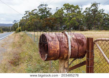 Bruny Island Tasmania Australia - 18 December 2016: rusty rural barrel letterbox on farm gate
