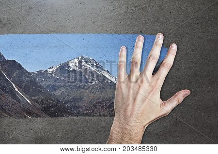 Male hand wiping concrete background and revealing mountain view. Creativity concept