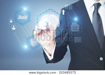 Businessman drawing abstract digital business hologram on blue background. Antivirus concept