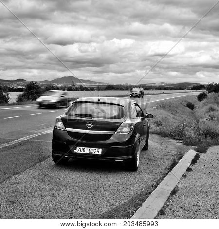 Ceske Stredohori, Czech Republic - August 12, 2017: Black Car Opel Astra H Stand By Road Between Fie