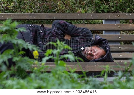 KAZAN, RUSSIA - 9 SEPTEMBER 2017: homeless alcoholic beggar man is sleeping on bench in park, telephoto shot
