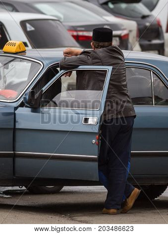 Russian illegal taxi and driver in tatar national hat, vertical, telephoto