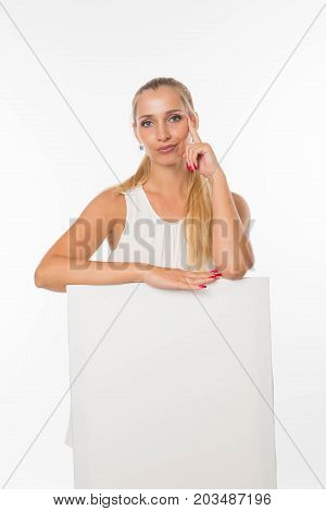 Young displeased woman portrait of a confident businesswoman showing presentation, pointing placard gray background. Ideal for banners, registration forms, presentation, landings, presenting concept.