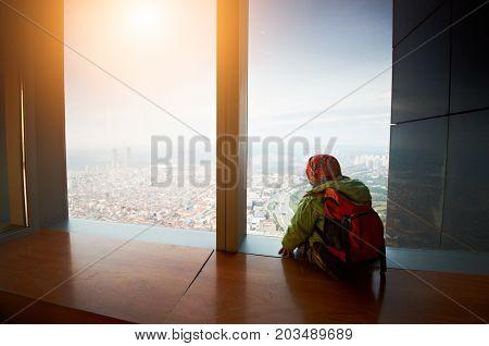 little boy walking on a roof of a skyscrapper