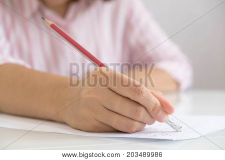 Closeup Of Woman's Hand Writing On Paper. Close Up Of Lady's Hand Writing In Notepad Placed On Deskt