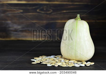 Butternut pumpkin and seeds on dark wooden background