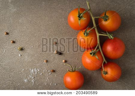 Top view of a bunch of natural cherry tomatoes on cement background with copy space.