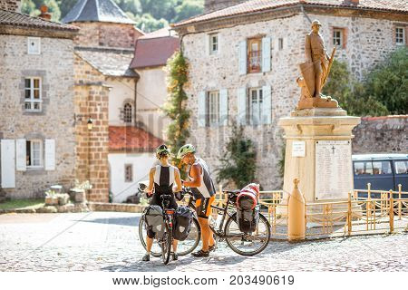 BLESLE, FRANCE - August 01, 2017: View on the old square with couple on the bicycles in Blesle village in Auvergne region of France