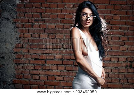 Sexy Seductive Cheeky Girl In A White T-shirt, Stands On The Background Of A Brick Wall And Pulls Ba
