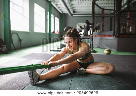 A Beautiful Girl With A Smile Stretches Her Muscles, Kneads, Warms Up Before Training In A Joint Wit