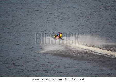 Two men are swiftly moving on a water motorcycle. Transport