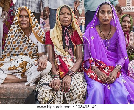 AGRA, INDIA - NOVEMBER 19 2016: Three women in colorful saris and hijabs sit near the entrance to the Great Gate of the Taj Mahal in Agra, India