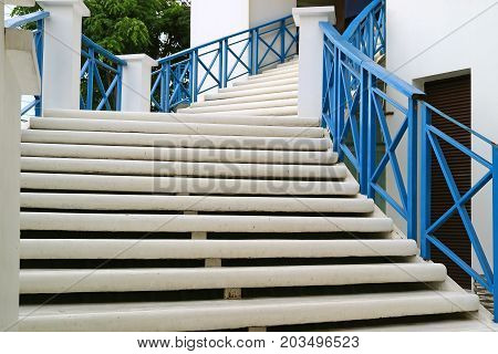 White outdoors staircase with blue railing leads to the upstairs