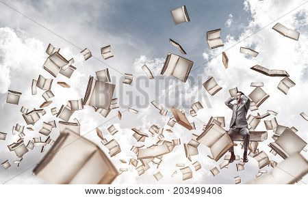 Frustrated businessman sitting on big book and closing ears with hands