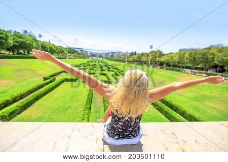 Happy tourist woman with open arms at Miradouro Park Eduardo VII in Lisbon, Portugal, Europe. Blonde female looking a gardens of park, Marquess of Pombal Statue and Avenida da Liberdade. Sunny day.