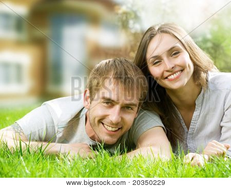 Happy Couple near their House.Smiling Family outdoor.Real Estate