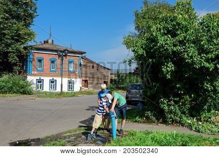 SUZDAL/ RUSSIA - AUGUST 19, 2017. Three boys playing with a public water tap on the street near the old wooden residential house. Suzdal, Vladimir region, Russia
