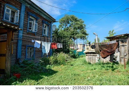 Winter and summer clothes hanging on the line in the backyard of the old wooden residential house. Suzdal, Vladimir region, Russia