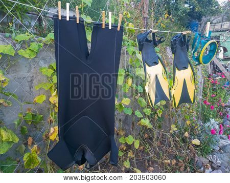 wetsuit mask fins dry on rope after swimming in the garden