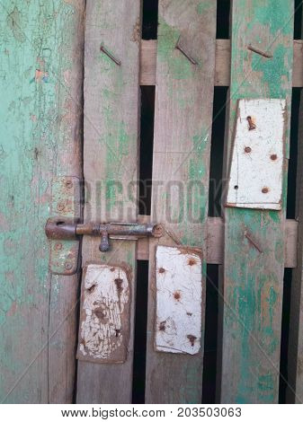 Old rusty bolt and padlock on a wooden door