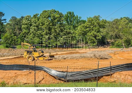 A construction site where dirt work has been done to prepare the land for a building project. The area has been fenced off to the public to prevent anyone from being injured.