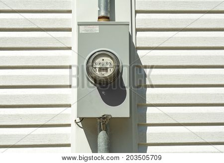 An older residential analog electric power meter on a white vinyl sided house.