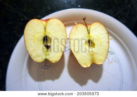 Two apple halves lie on a plate, on top of a black granite counter top.