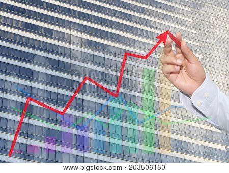 hand of businessman using red pen pointing to top business graph on Glass wall background of tall buildingsconcept of investment and profits.