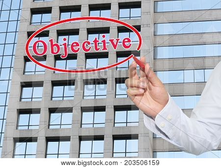 hand of businessman using red pen pointing to text of objective on glass window of tall building backgroundconcept of investment and benefit.