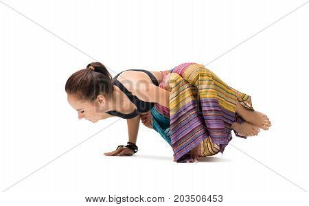 Slim girl striped sarong wraped over her body doing yoga indoors isolated on shot white background