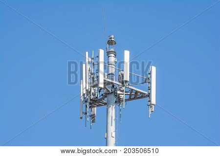 A telecommunications tower isolated on blue sky background. The tower provides the power to send and receive high numbers of cellular telephone calls per day for the customers.