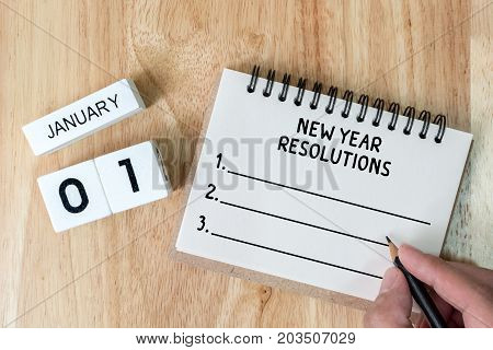 Top view notebook and calendar on wood table New year resolution concept