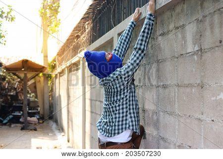 Masked burglar climbs through a fence. Catch burglar concept