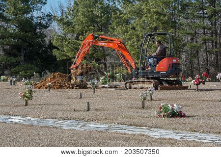 Calhoun City, MS USA - January 27,  2017- An african american man digging a grave at a rural cemetery.