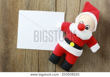 Santa Claus doll on wooden background and have note paper copy space for your design in your work backdrop.
