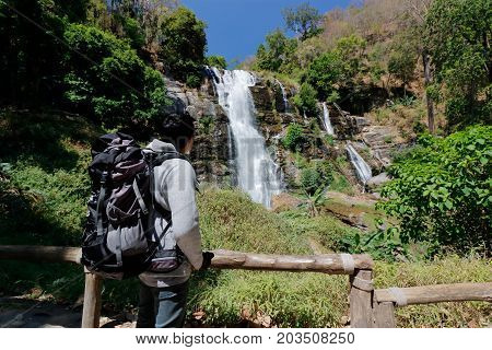 Young Asian tourist with backpack looking at Wachirathan waterfall in Doi Inthanon Chiang Mai Thailand