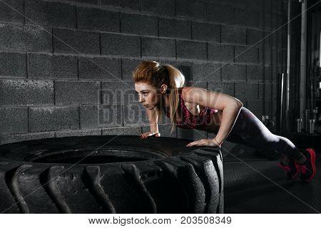 Sportswoman. Fit Sporty Woman Doing Push Ups On Tire Strength Po