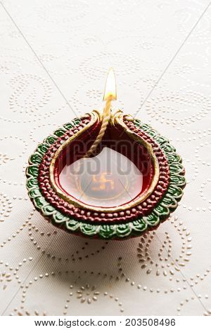 stock photo of beautiful diwali diya, isolated over decorative background, moody lighting and selective focus
