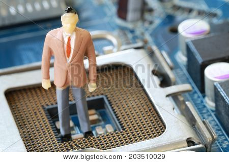 Businessman doll Stand on a computer motherboard in concept of doing business and profiting on technology.