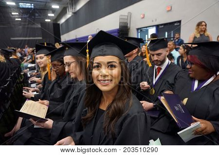 JOLIET, ILLINOIS / UNITED STATES - MAY 12, 2017: Happy graduates of Joliet Junior College hold their awarded diplomas in their seats at their commencement ceremony.