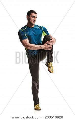 Fitness strong male athlete warming up legs on white background