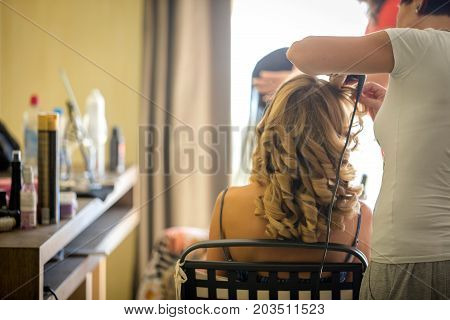 Hair stylist curling iup the hair of a young caucasuian lady.