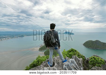 Wide angle shot of hipster young Asian man with backpack standing on the stone on the mountain and looking into the distance at sea bay